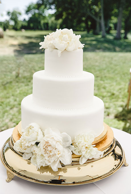 A three-tiered white wedding cake with piped details and fresh flowers created by Confectionery Designs.