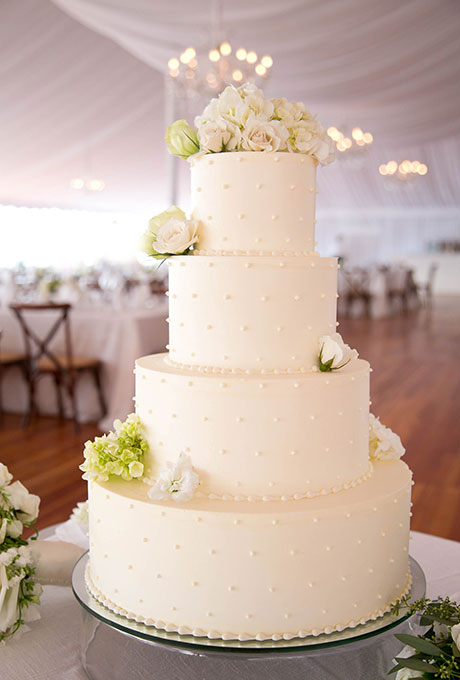 A four-tiered white wedding cake with piped dot details, created by Kennedy Confections.