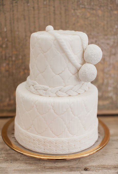A two-tiered nautical white wedding cake with braided details and roping, created by La Patisserie Chouquette.