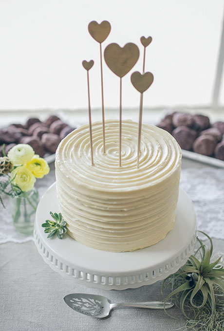 A simple one-tier white wedding cake with heart toppers created by Cake Monkey Bakery.