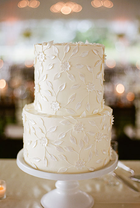 A two-tier white wedding cake with delicate flower details created by Jim Smeal.